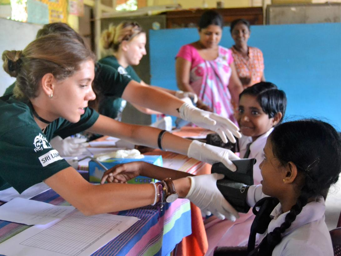 A clinical volunteer abroad measures the blood pressure of a young child in Sri Lanka.